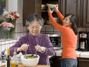 Older woman preparing salad in kitchen, younger woman reaching up into cupboard for bowls.