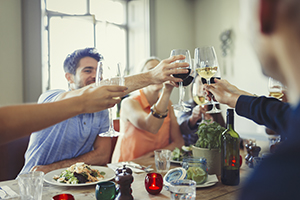 Friends celebrating by toasting at a restaurant table