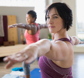Two women in exercise clothing, doing yoga in a class